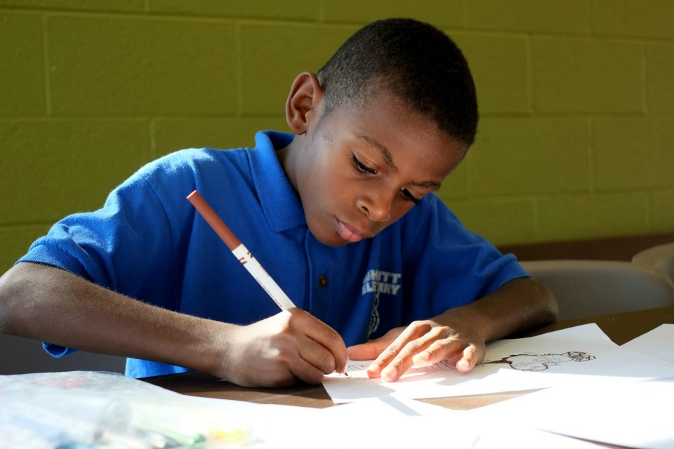 Child doing homework. Image by Feeding America. CC BY 2.0