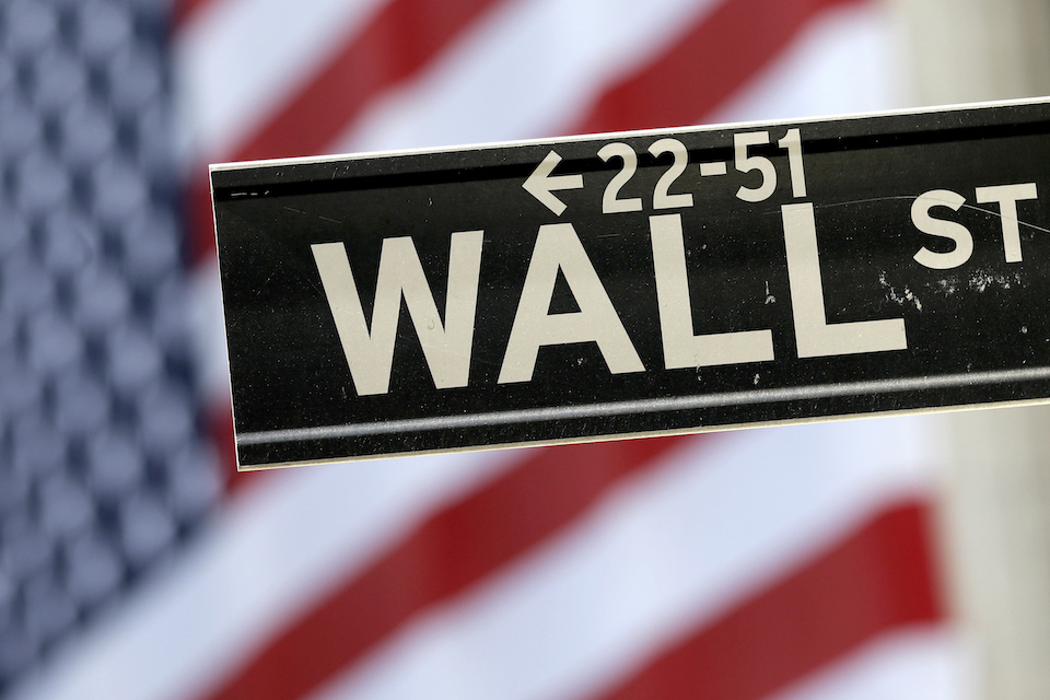 A Wall Street street sign is framed by an American flag hanging on the facade of the New York Stock Exchange, Tuesday, Sept. 8, 2015. The financial crisis that struck in 2008 touched off the worst recession since the 1930s Great Depression, wiping out $11 trillion in U.S. household wealth and leaving about 8 million Americans jobless. More than 5 million families lost their homes to foreclosure. Reckless trading and aggressive practices on Wall Street in the prior boom years were pinned with much of the blame. In the aftermath, Congress enacted an overhaul of financial rules aimed at preventing another meltdown and multibillion-dollar taxpayer bailout of banks. (AP Photo/Mary Altaffer, File)