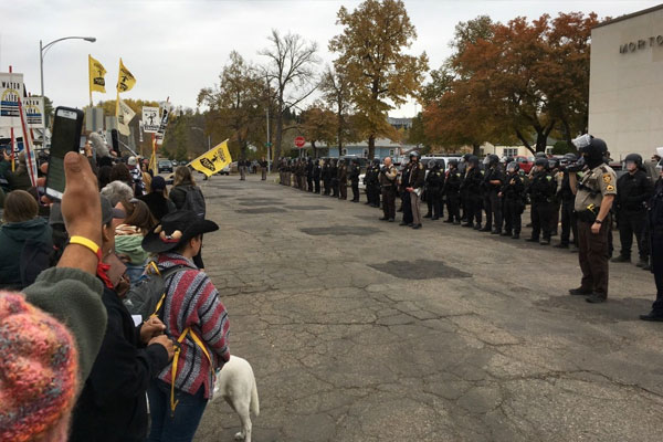 Police officers line up as a protest grows outside the Morton County Courthouse in Mandan, N.D., Monday, Oct. 17, 2016. A judge dismissed a complaint Monday against Democracy Now journalist Amy Goodman, who reported on a clash between pipeline protesters and private security in September. (Mike McCleary/The Bismarck Tribune via AP)