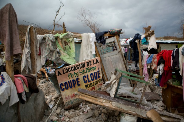 A sign in French announcing a music concert sits among salvaged clothes drying on the remains of a home destroyed by Hurricane Matthew in Port-a-Piment, Haiti, Monday, Oct. 10, 2016. Nearly a week after the storm smashed into southwestern Haiti, some communities along the southern coast have yet to receive any assistance, leaving residents who have lost their homes and virtually all of their belongings struggling to find shelter and potable water. (AP Photo/Rebecca Blackwell)
