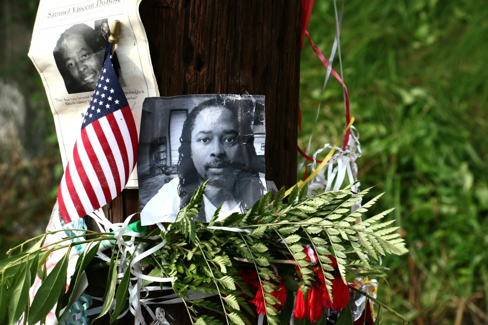 In this July 29, 2015, file photo, photos of Sam DuBose hang on a pole at a memorial near where he was shot and killed by a University of Cincinnati police officer during a July 19, 2015, traffic stop in Cincinnati. Former University of Cincinnati police officer Ray Tensing, facing trial on charges of murder and voluntary manslaughter, was due back in court for a Friday, Oct. 14, 2016, pretrial hearing, ahead of the planned start of jury selection on Oct. 25, 2016. (AP Photo/Tom Uhlman, File)