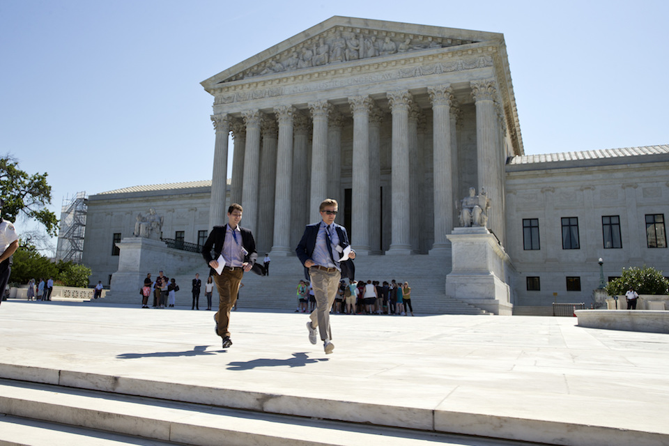 Runners leave the Supreme Court in Washington with papers announcing court decisions, June 20, 2016. The Supreme Court is set to begin its new term as it ended the last one, down one justice and ideologically deadlocked on a range of issues. The absence of a ninth justice since Antonin Scalia's death in February has hamstrung the court in several cases and forced the justices to look for less contentious issues on which they are less likely to divide by 4-4 votes. (AP Photo/Alex Brandon, File)