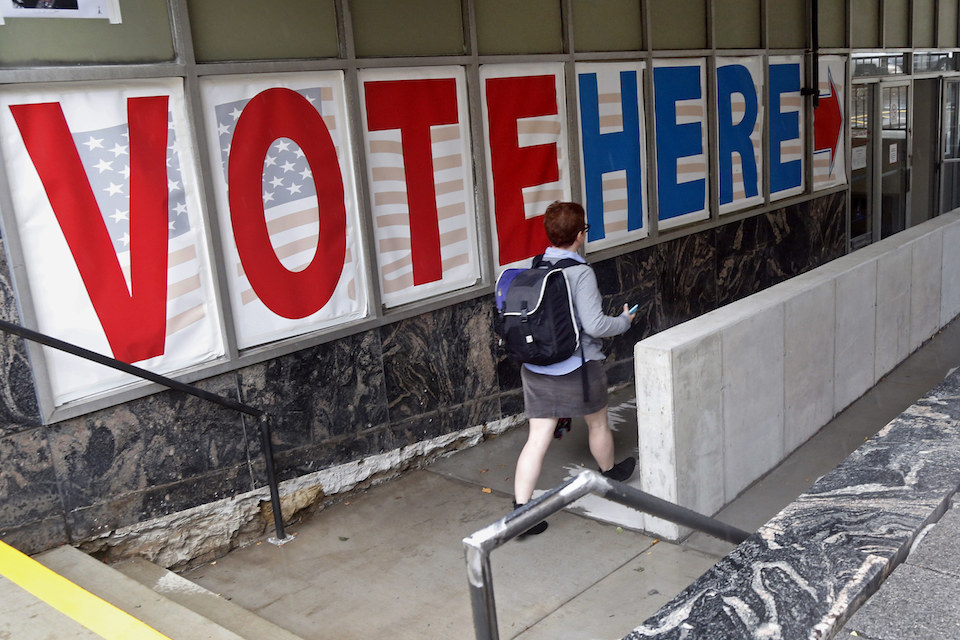 A voter passes a large sign before voting in Minneapolis, Sept. 23, 2016. If Donald Trump or Hillary Clinton scores a high note or commits a blunder in Sunday's presidential debate, millions of voters can respond almost immediately. They can fill out a mail-in ballot right away, or head to a polling location the next day. (AP Photo/Jim Mone, File)