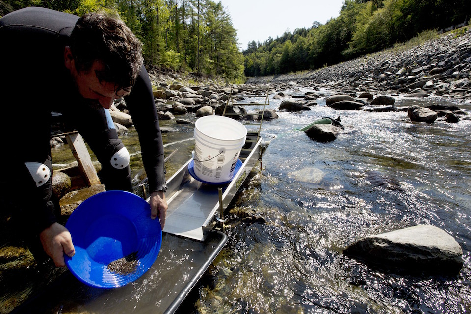 Chris Hall uses a sluice box to pan for gold in the Wild Ammonoosuc River in Bath, N.H. Sunday, Sept. 4, 2016. A new generation of gold miners is giving prospecting a try, especially in New England and the Pacific Northwest. But more are turning to machinery, and that's causing problems. Environmentalists complain mechanized mining poses a threat to river systems. Some states are banning certain mining techniques deemed harmful. (AP Photo/Jim Cole)