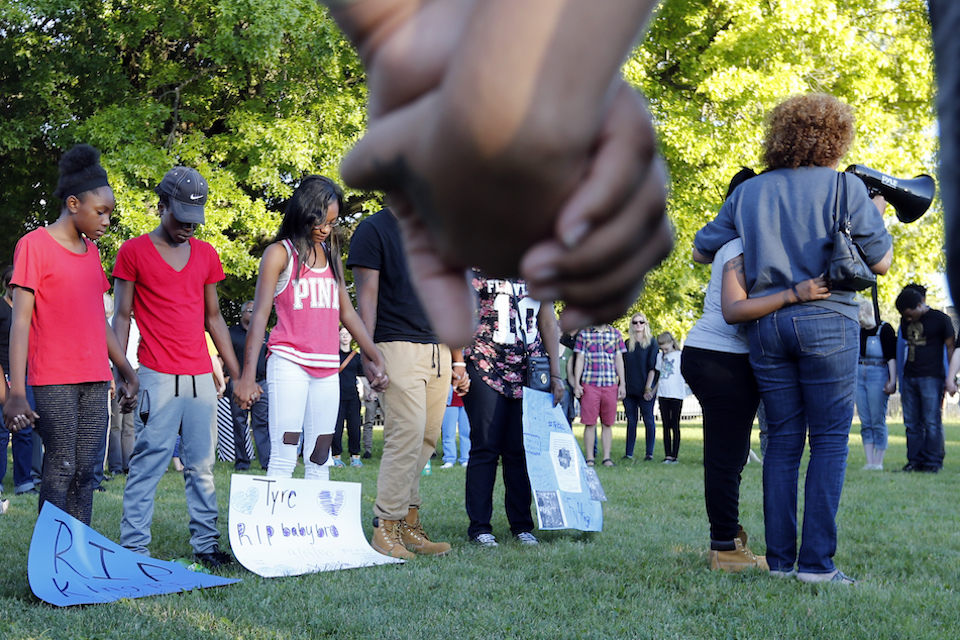 Members of Tyre King's family hold hands while listening to prayer during a vigil for 13-year-old Tyre King Thursday, Sept. 15, 2016, in Columbus, Ohio. King was shot and killed by Columbus police Wednesday evening. (AP Photo/Jay LaPrete)