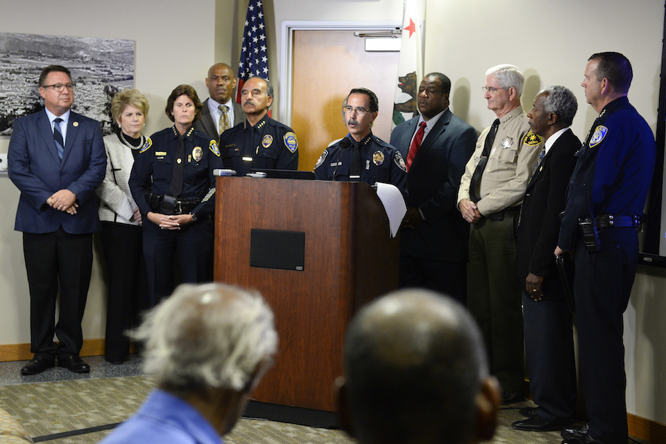 El Cajon Police Department Capt. Jeffery Davis, center, speaks at a news conference on Friday Sept. 30, 2016, in El Cajon, Calif, held to address the killing of Alfred Olango, a Ugandan refugee shot by an El Cajon police officer on Tuesday. The El Cajon police department released video footage of the shooting at the news conference. (AP Photo/Denis Poroy)