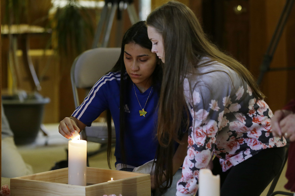 Rachel Marsh, 15, right, and Selena Orozco, 15, left, carry flowers and light a candle as they attend a prayer service, Saturday, Sept. 24, 2016, at the Central United Methodist Church in Sedro-Woolley, Wash. The service was held in regard to Friday's fatal shooting of several people at a Macy's department store at the Cascade Mall in nearby Burlington, Wash. Both girls said they knew one of the victims of the shooting. (AP Photo/Ted S. Warren)