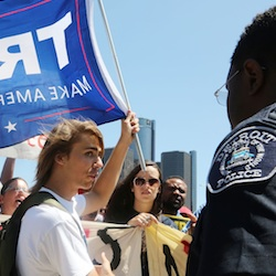 As Republican presidential candidate Donald Trump speaks inside to a business crowd at the Detroit Economic Club, protesters against Trump and supporters of Trump, like Zack Wojtan of Detroit, who waves his Trump flag, demonstrate outside Cobo Center Monday, Aug. 8, 2016, in downtown Detroit. (Regina H. Boone/Detroit Free Press via AP)