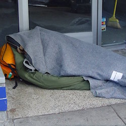 Homeless person sleeping in doorway by Franco Folini
