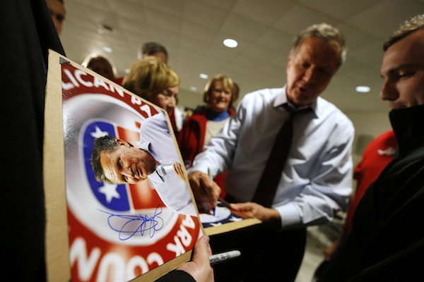 Republican presidential candidate Ohio Gov. John Kasich signs photos for supporters after a town hall meeting Wednesday, Dec. 16, 2015, in Ankeny, Iowa. (Michael Zamora/The Des Moines Register via AP)