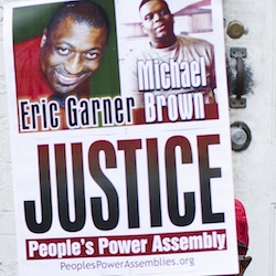 A demonstrator holds a sign bearing the likeness of Eric Garner and Michael Brown before a march to protest the death of Garner in the Staten Island borough of New York. On Friday, Jan. 8, 2016, New York Police Department Sgt. Kizzy Adonis has been stripped of her gun and badge and charged internally in Garner's death. It's the first official accusation of wrongdoing in the case that helped spark a national movement on the role of race in policing. (AP Photo/John Minchillo, File)