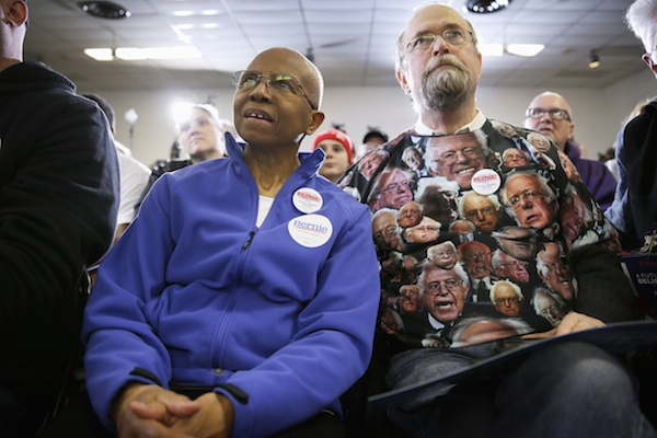 In this Jan. 26, 2016, photo, Kittie Weston-Knauer and her husband Max Knauer of Des Moines, Iowa, listen as Democratic presidential candidate, Sen. Bernie Sanders, I-Vt. speaks during a stop at the United Steelworkers Local 310L union hall in Des Moines, Iowa. Donald Trump, Ted Cruz and Bernie Sanders are energizing grassroots voters as the first balloting of the 2016 presidential race draws near. Yet the three maverick contenders are also alarming political operatives over the damage each could wreak on their own parties' House candidates this November. (AP Photo/Charlie Neibergall)