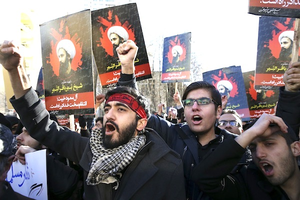 Iranian demonstrators chant slogans during a protest denouncing the execution of Sheikh Nimr al-Nimr, a prominent opposition Shiite cleric in Saudi Arabia, seen in posters, in front of the Saudi Embassy, in Tehran, Sunday, Jan. 3, 2016. Saudi Arabia announced the execution of al-Nimr on Saturday along with 46 others. His execution drew condemnation from Shiites across the region. (AP Photo/Vahid Salemi)