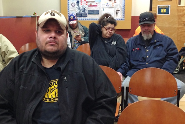 In this Jan. 28, 2016 photo, Joe Heflin, left, of Jefferson City, waits with others for his turn to receive free groceries from the Samaritan Center food pantry in Jefferson City, Mo. Heflin, 33, also receives federally funded food stamp benefits. He is among the more than 1 million people nationwide whose food stamps could end in three months if he doesn't meet work requirements or receive a disability exemption. (AP Photo/David A. Lieb)