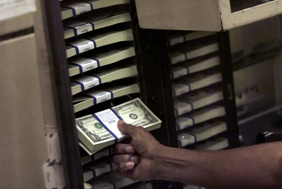 A Bureau of Printing and Engraving employee checks one dollar bills at the plant in Washington, April 24, 2001. When the bills are due, more young blacks and Latinos feel like they can't turn to Mommy, Daddy or even Grandma to help them out of financial trouble than whites or Asians, according to a new Associated Press poll. (AP Photo/Hillery Smith Garrison, File)