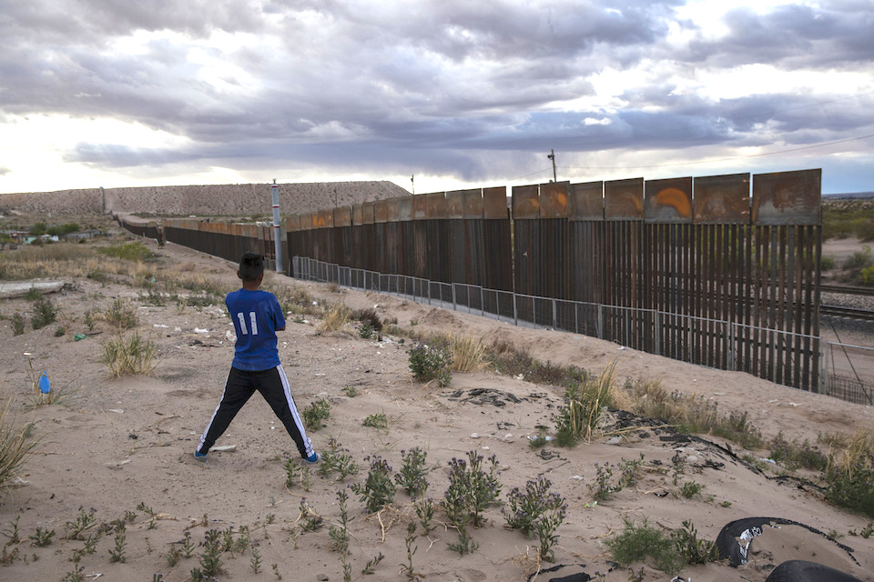 a youth looks at a new, taller fence being built along U.S.-Mexico border, replacing the shorter, gray metal fence in front of it, in the Anapra neighborhood of Ciudad Juarez, Mexico, across the border from Sunland Park, New Mexico. Most Americans oppose funding President Donald Trump's wall along the U.S.-Mexico border. That's according to a poll released Thursday by The Associated Press-NORC Center for Public Affairs Research. (AP Photo/Rodrigo Abd, File)