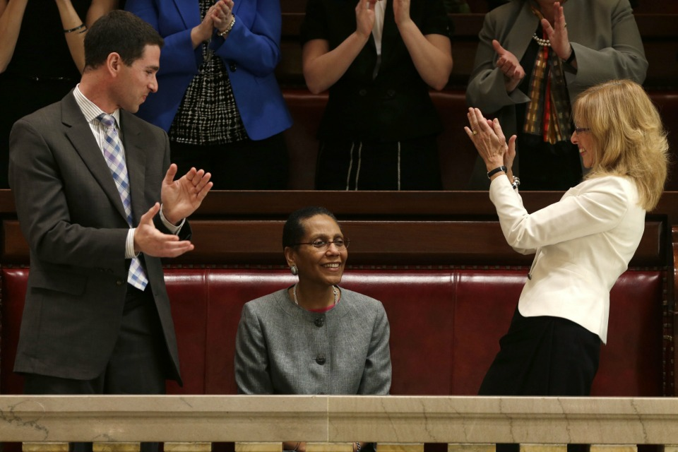 Justice Sheila Abdus-Salaam, center, receives applause after her confirmation to serve on the New York State Court of Appeals from Craig Alfred of Gov. Andrew Cuomo's appointments office, left, and Albany City Court Judge Rachel Kretser