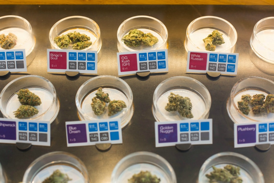 Cannabis flowers with quality testing results on display at a dispensary