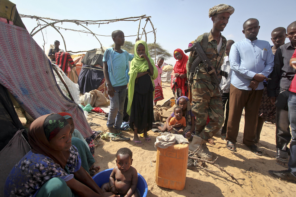 A Somali soldier provides security as newly displaced Somalis gather at a camp in the Garasbaley area on the outskirts of Mogadishu, Somalia, March 28, 2017. Drought-stricken families facing a hunger crisis are on the move, trying to reach international aid agencies that cannot distribute food in areas under the control of al-Shabab, Somalia's homegrown Islamic extremist rebels who are affiliated to al-Qaida. Week by week, country by country, the Pentagon is quietly seizing more control over warfighting decisions, sending hundreds of more troops to war with little public debate and seeking greater authority to battle extremists across the Middle East and Africa. This week it was Somalia, where President Donald Trump gave the U.S. military more authority to conduct offensive airstrikes on al-Qaida-linked militants.(AP Photo/Farah Abdi Warsameh)