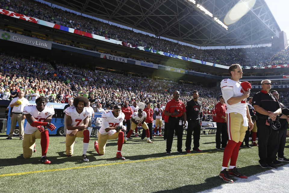 San Francisco 49ers Blaine Gabbert, right, stands as Eli Harold (58), Colin Kaepernick (7) and Eric Reid (35) kneel during the national anthem before an NFL football game against the Seattle Seahawks in Seattle, Sept. 25, 2016. What started as a protest against police brutality has mushroomed a year later into a divisive debate over the future of Kaepernick who refused to stand for the national anthem and now faces what his fans see as blackballing for speaking out in a country roiled by racial strife. The once-rising star and Super Bowl quarterback has been unemployed since March, when he opted out of his contract and became a free agent who could sign with any team. (AP Photo/Ted S. Warren, File)