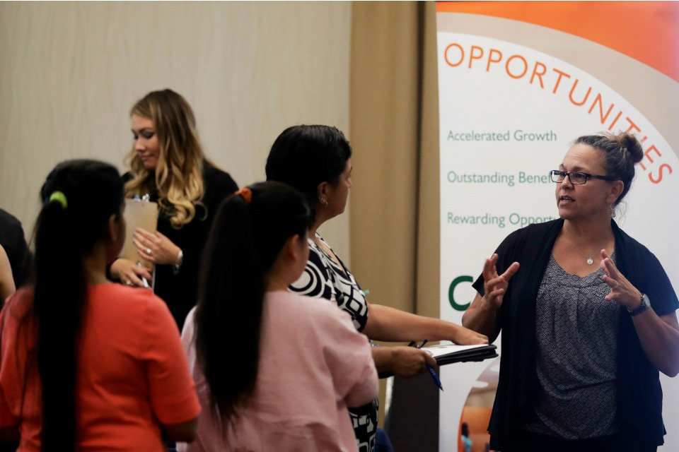 In this Thursday, Aug. 24, 2017, photo, Kathy Tringali, right, a recruiter for retailer Big 5 Sporting Goods, talks to job seekers during a job fair in San Jose, Calif.