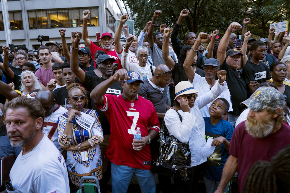 Supporters of unsigned NFL quarterback Colin Kaepernick mingle with passers-by on the sidewalk, foreground, Wednesday, Aug. 23, 2017, in front of NFL headquarters in New York. (AP Photo/Craig Ruttle)