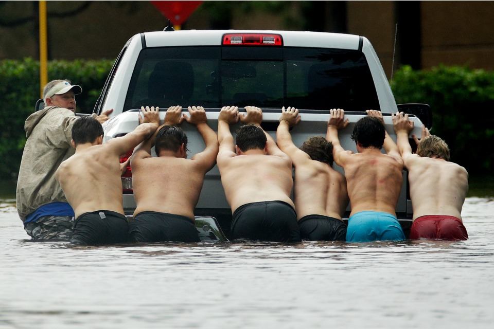 People push a stalled pickup through a flooded street in Houston, after Tropical Storm Harvey dumped heavy rains, Sunday, Aug. 27, 2017.