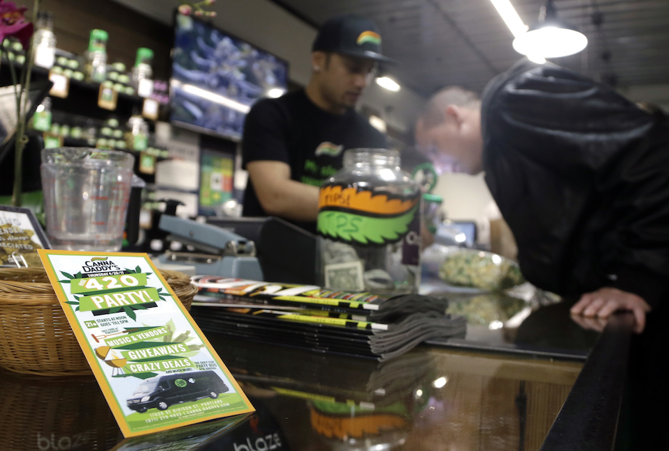 Tyler Kennedy, right, smells a marijuana sample from Noah Siialata at CannaDaddy's Wellness Center marijuana dispensary in Portland, Ore. April 20, 2017. Officials in states like Oregon where marijuana is legal are trying to curtail smuggling of pot to other states. Meanwhile, U.S. Attorney General Jeff Sessions is pushing for a more aggressive approach in these states, noting the drug is being diverted to other states. (AP Photo/Don Ryan)