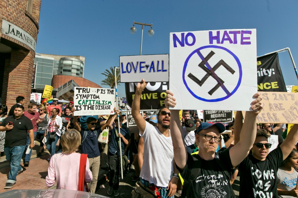 In this Aug. 13, 2017, file photo, demonstrators march in downtown Los Angeles decrying hatred and racism the day after a white supremacist rally that spiraled into violence in Charlottesville, Va. (AP Photo/Damian Dovarganes, file)