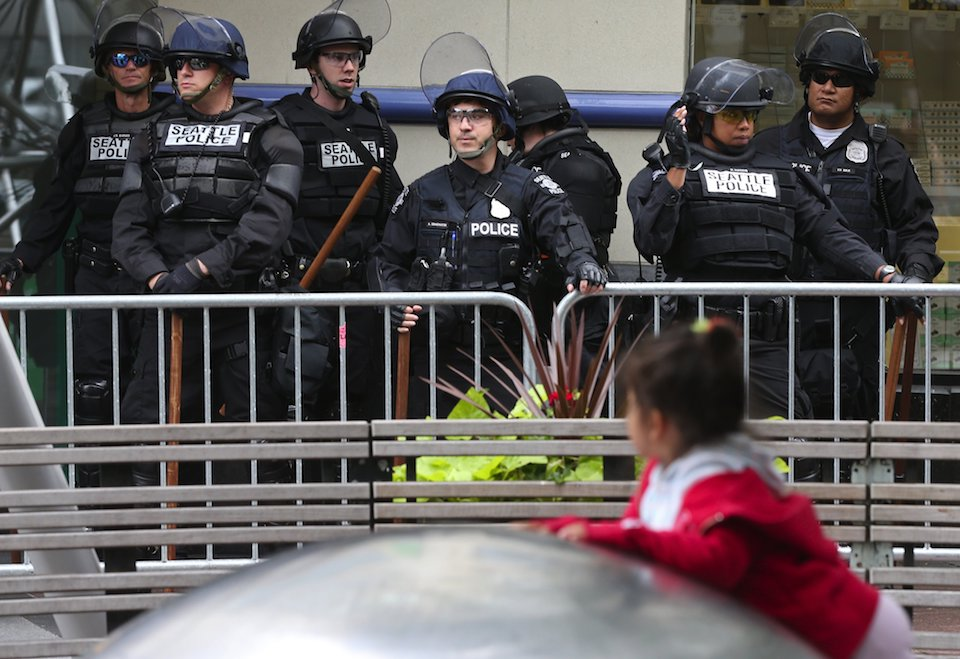 "A child plays near Seattle Police before a pro-Trump ""Prayer Rally"" at Westlake Park, Sunday, Aug. 13, 2017, in Seattle. A counter group holds its own rally nearby. (Ken Lambert/The Seattle Times via AP)"