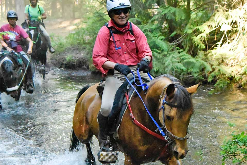 Jeff Tryens on horse in river