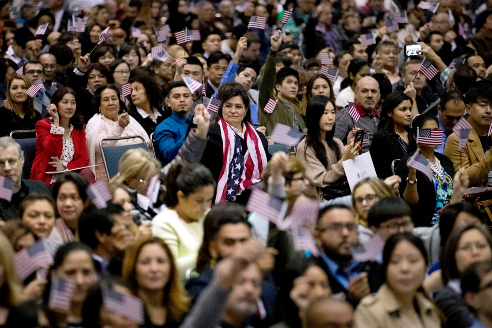 People wave U.S. flags during a naturalization ceremony at the Los Angeles Convention Center, in Los Angeles.