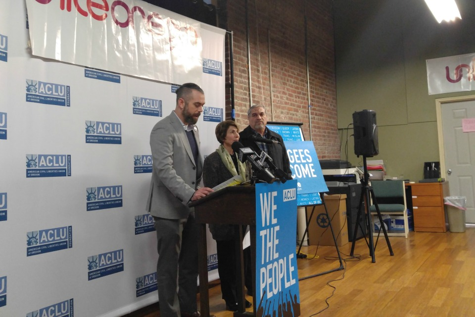 Mat dos Santos, legal director for ACLU of Oregon, speaks at a Feb. 1 press conference with Manije Mehrnoosh, Unite Oregon board co-chair and Muwafaq Alkattan, Unite Oregon staff member and Iraqi refugee.