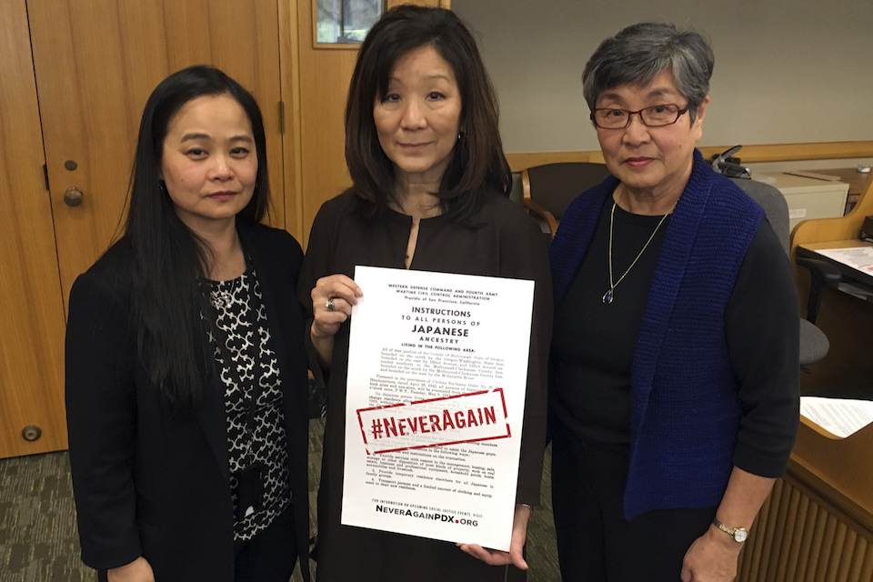 Carol Suzuki, Lynn Fuchigami Longfellow, middle and June Arima Schumann on Monday, Feb. 13, 2017, display a copy of a poster in a hearing room in the Oregon State Capitol that notified Japanese-Americans they would be sent to relocation camps. The slogan #NeverAgain has been emblazoned on the poster. Seventy-five years ago, America's president signed an executive order that incarcerated 120,000 Japanese Americans. Now, the survivors, descendants and activists are backing a bill in the Oregon Legislature to make the anniversary a Day of Remembrance, underscoring that this should never happen again, against any group. (AP Photo/Andrew Selsky)
