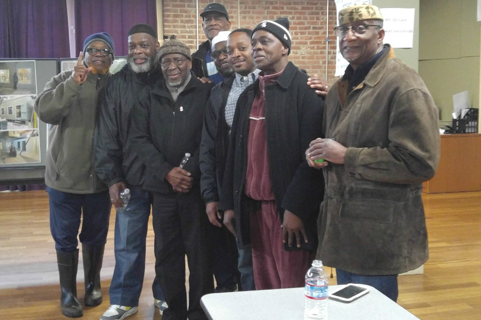 Omar Shabazz (left), Deerk Rasheed, Imam Muhammad A. Najieb, Imam Mikal Shabazz, Waleed Sadruddin, Hakeem Muhammad, Wesley Salauddin (Johnson ), and Wali Lucas (standing behind line) pose for a photo at a Feb. 18 open house to raise funds for a new physical space for the Muslim Community Center of Portland.