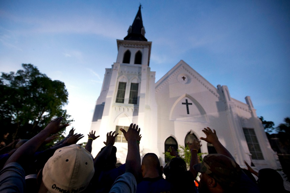 The men of Omega Psi Phi Fraternity Inc. lead a crowd of people in prayer outside the Emanuel AME Church, after a memorial for the nine people killed by Dylann Roof in Charleston, S.C.