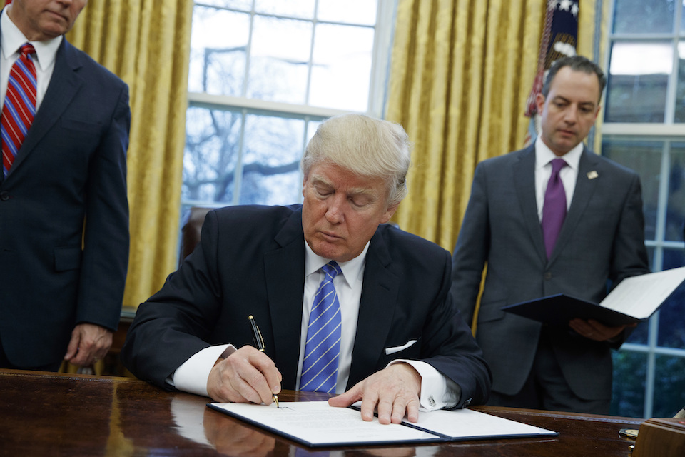 President Donald Trump signs an executive order to withdraw the U.S. from the 12-nation Trans-Pacific Partnership trade pact agreed to under the Obama administration in the Oval Office of the White House in Washington, Jan. 23, 2017. (AP Photo/Evan Vucci, File)