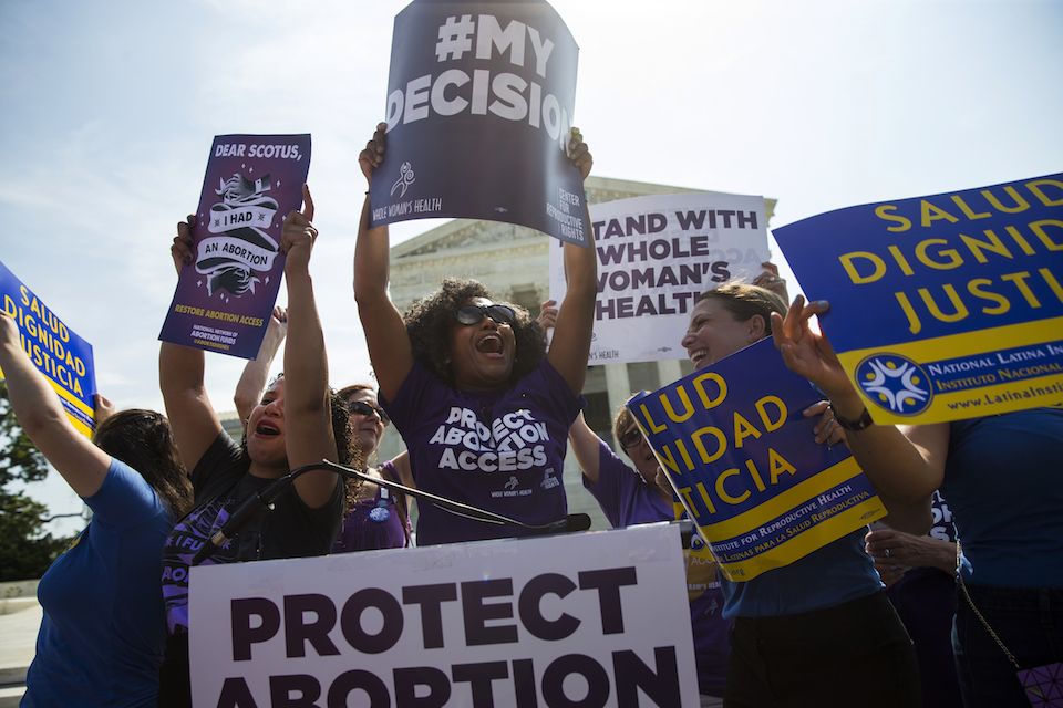 Activists celebrate during a rally on abortion rights at the Supreme Court in Washington, June 27, 2016. The tens of thousands of women flocking to Washington for a march on the day after Donald Trump's inauguration come packing a multitude of agendas, but are united in their loathing for Trump. (AP Photo/Evan Vucci, File)