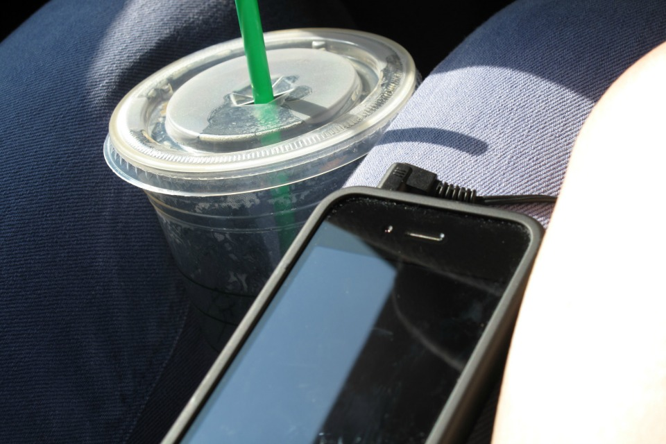 cell phone and coffee in front seat of car