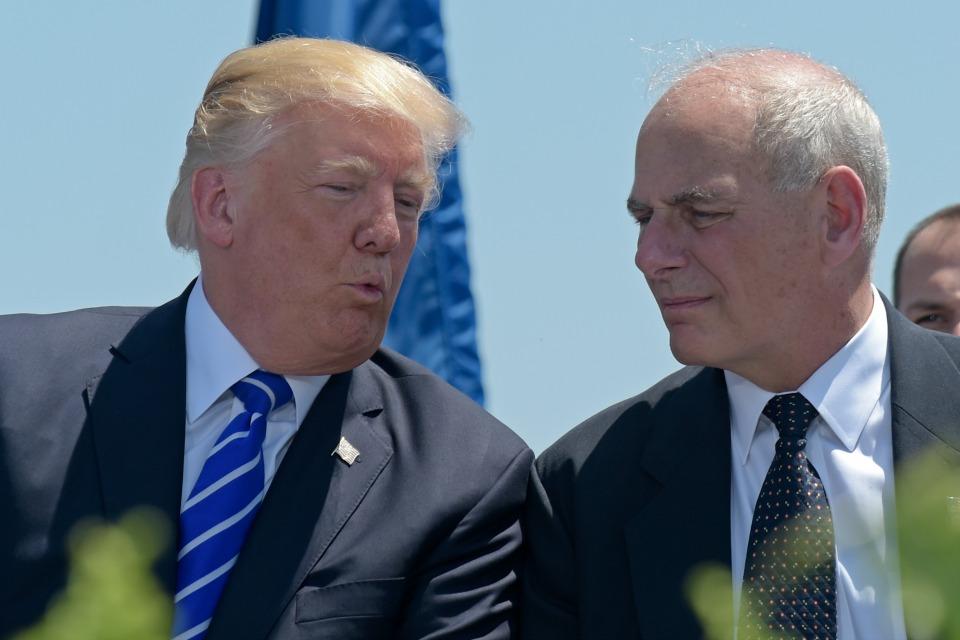 President Donald Trump talks with Homeland Security Secretary John Kelly during commencement exercises at the U.S. Coast Guard Academy in New London, Conn.