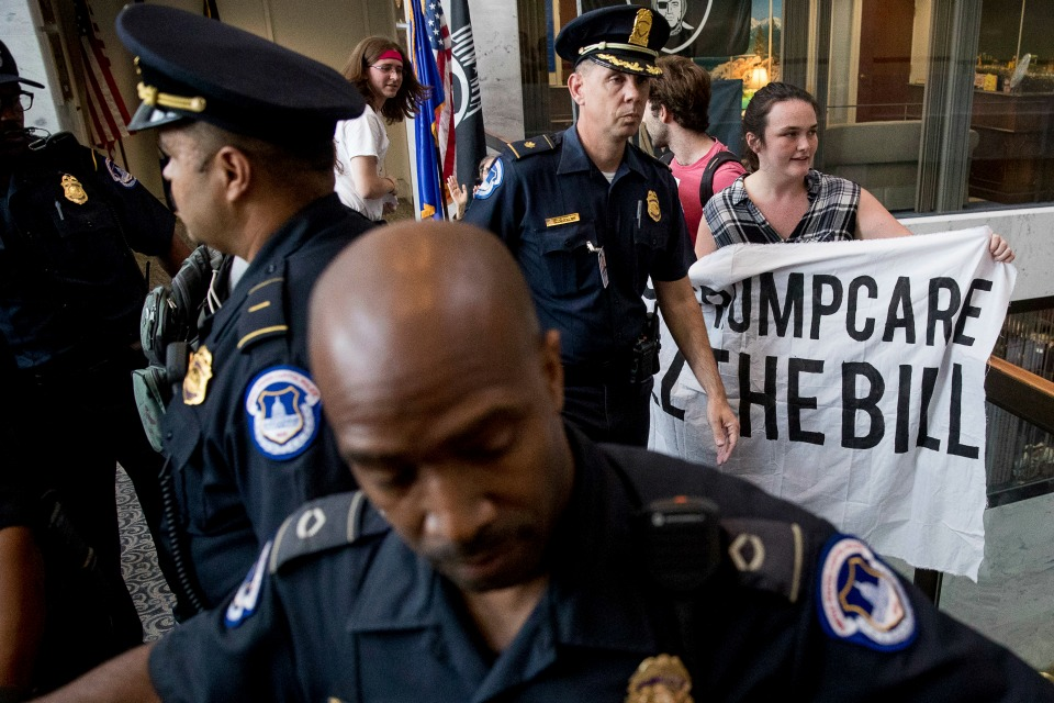 Capitol Hill police officers prepare to arrest a group protesting the republican healthcare bill outside the offices of Sen. Dean Heller, R-Nev., on Capitol Hill in Washington, Monday, July 17, 2017.