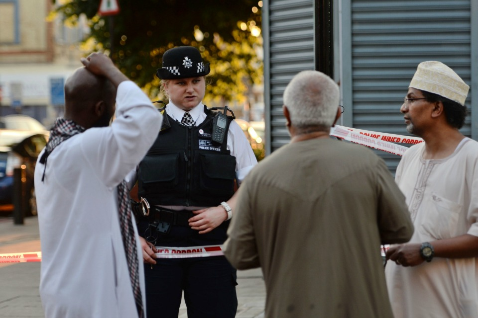 A police officer talks to local people at Finsbury Park in north London, where a vehicle struck pedestrians in north London Monday, June 19, 2017.