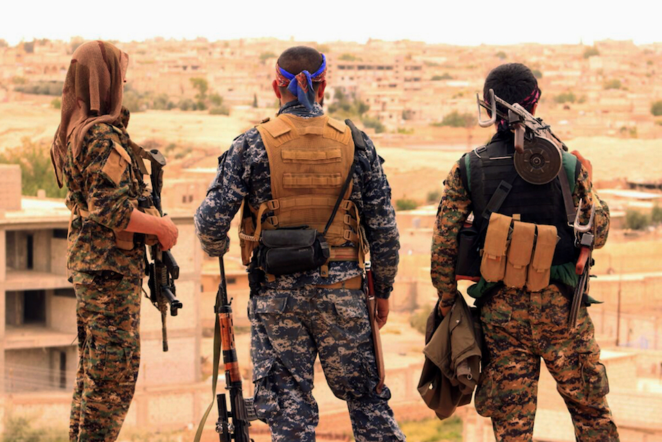 Fighters from the Syrian Democratic Forces looking toward the northern town of Tabqa, Syria, April 30, 2017. The U.S.-led coalition headquarters in Iraq said in a written statement that a U.S. F-18 Super Hornet shot down a Syrian government SU-22 on Sunday, June 18, after it dropped bombs near the U.S. partner forces, known as the Syrian Democratic Forces. The shootdown was near the Syrian town of Tabqa. (Syrian Democratic Forces via AP, File)