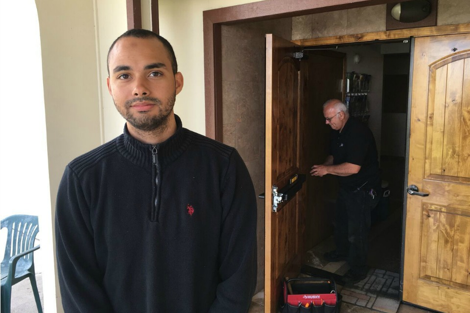 In this June 1, 2017, photo, Drew Williams, a member of the Eugene Islamic Center, poses for a portrait outside the building in Eugene, Ore., as locksmith Jim King upgrades the locks on the front doors.