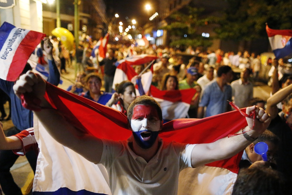 A youth holds a national Paraguay national flag as he marches with others in protest against the project to change the country's constitution, in Asuncion, Paraguay, Thursday, March 30, 2017. The country's upper house of Congress is split over a proposal to amend the constitution and allow for the re-election of former presidents. (AP Photo/Jorge Saenz)