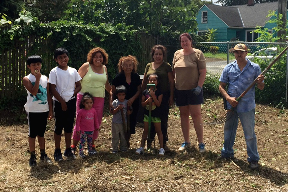 Young NE 72nd community gardeners join Elia Bracamontes Pulido (wearing bright green), Juan Herrera (center), Susana Pacheco (wearing dark green), Laurie Payton (second from right), and Pedro Mercado (baseball cap) at the groundbreaking / work party for the garden's Produce for People plot.