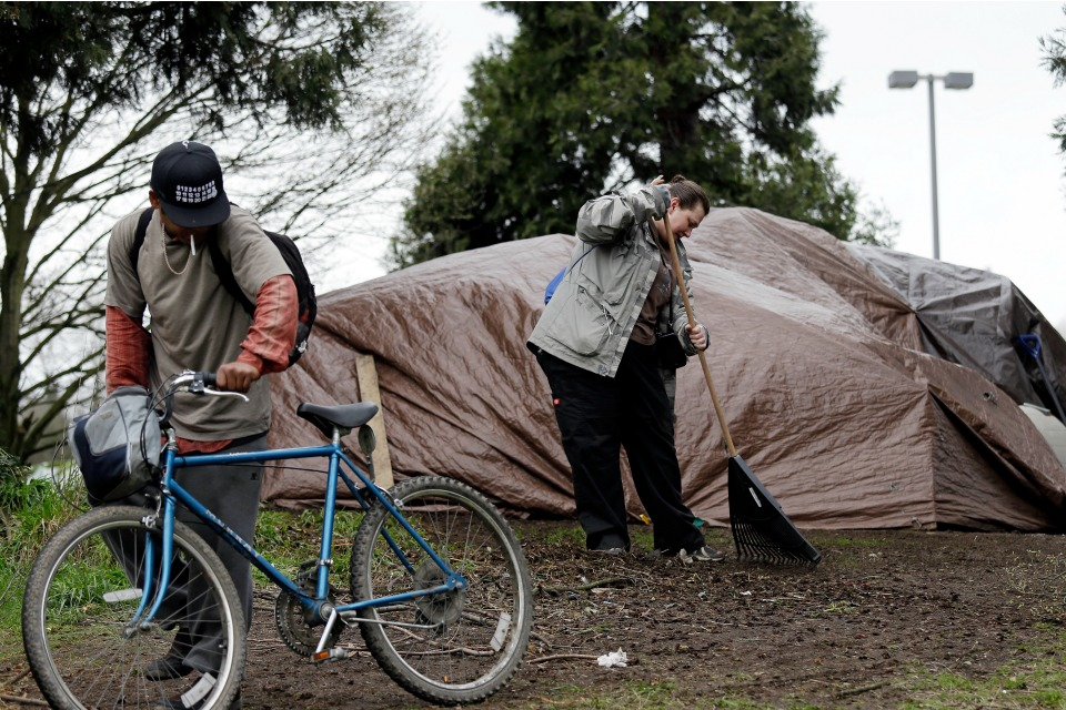 In this photo taken Thursday, March 23, 2017, Lisa Hooper rakes debris from in front of the tent where she lives in a greenbelt near a freeway, as another camper wheels a bicycle past her in Seattle.