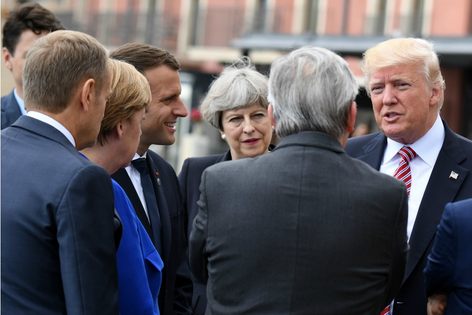 U.S. President Donald Trump, right, speaks to other G7 Leaders including British Prime Minister Theresa May, center, and French President Emmanuel Macron, third from left, in Taormina, Italy, Friday, May 26, 2017.