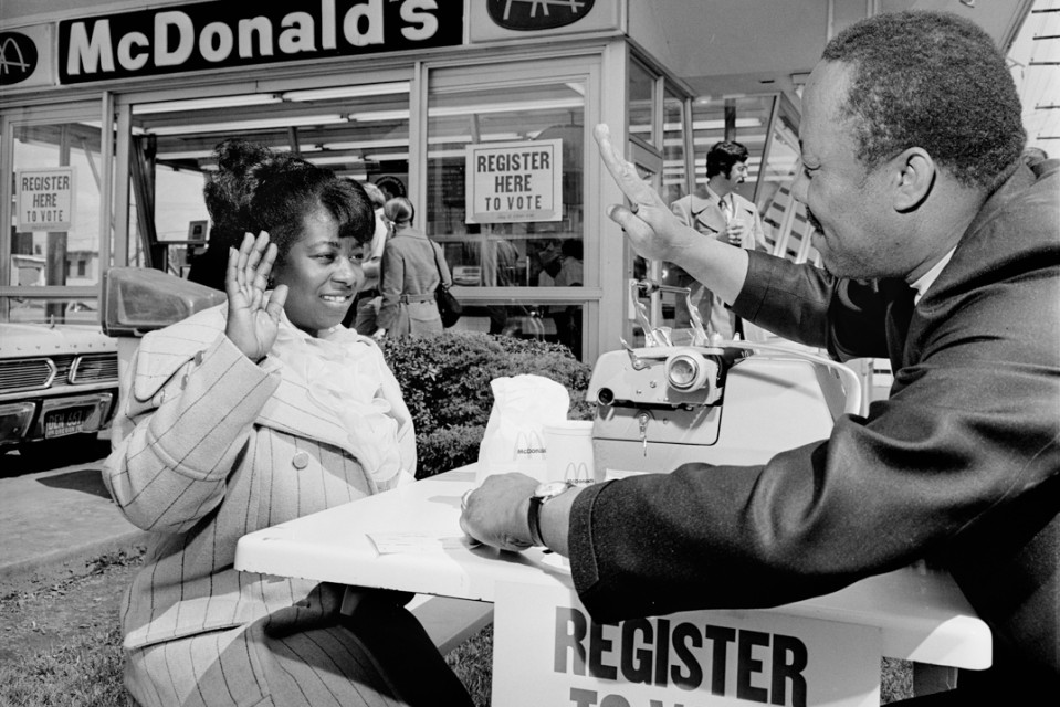 McDonalds, Union & Fremont. Voter registration drive. Nate Proby (president, United Minority Workers) administering oath to voter Francis Newman. April 18, 1972. (Allen deLay, 1915-2005)