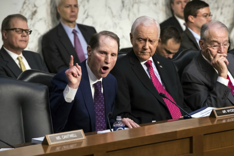 Sen. Ron Wyden, D-Ore., left, the top Democrat on the Senate Finance Committee, criticizes the Republican tax reform plan.